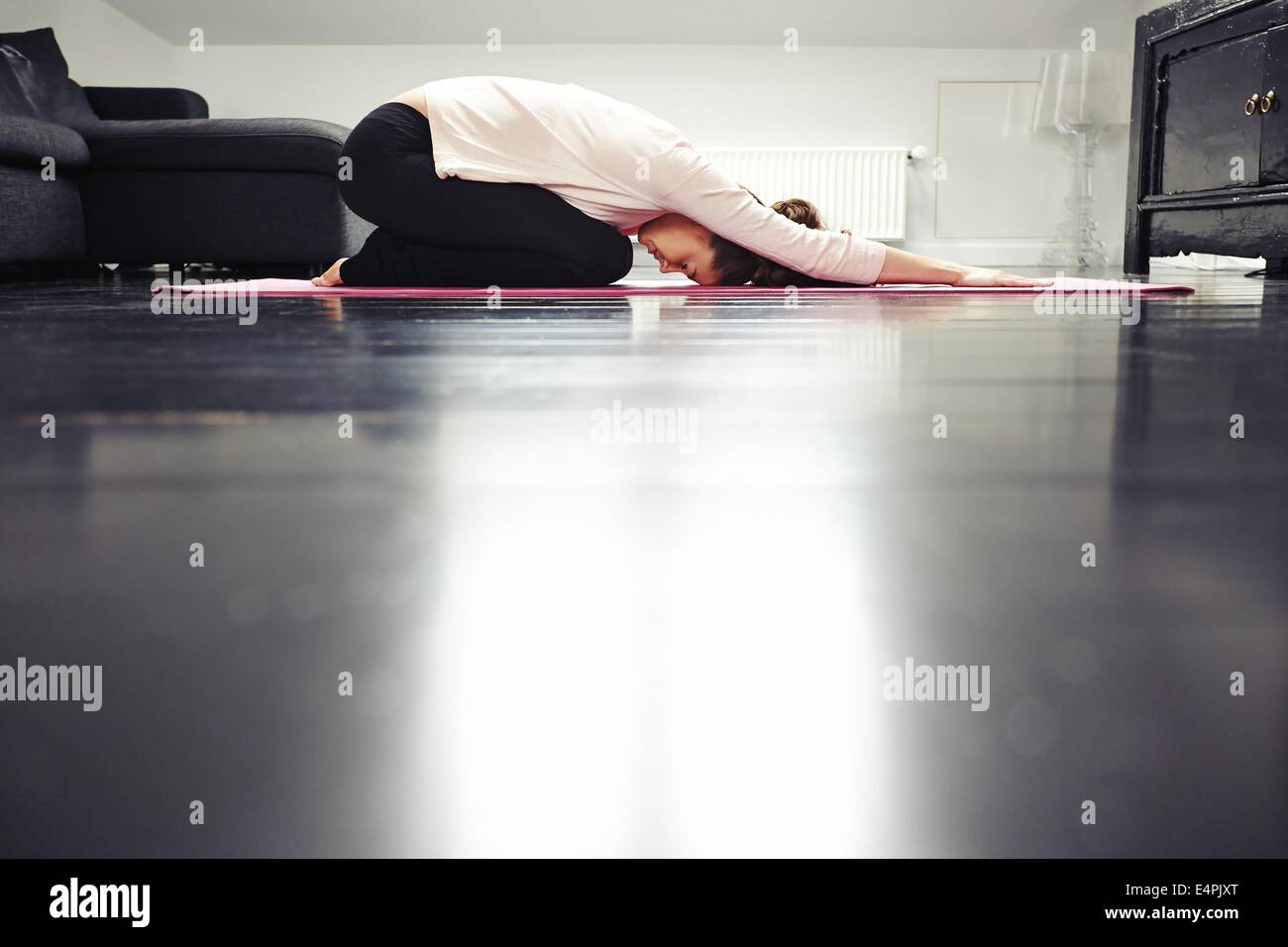 Side view of fit young lady practicing yoga at home. Healthy woman exercising in living room. - Stock Image