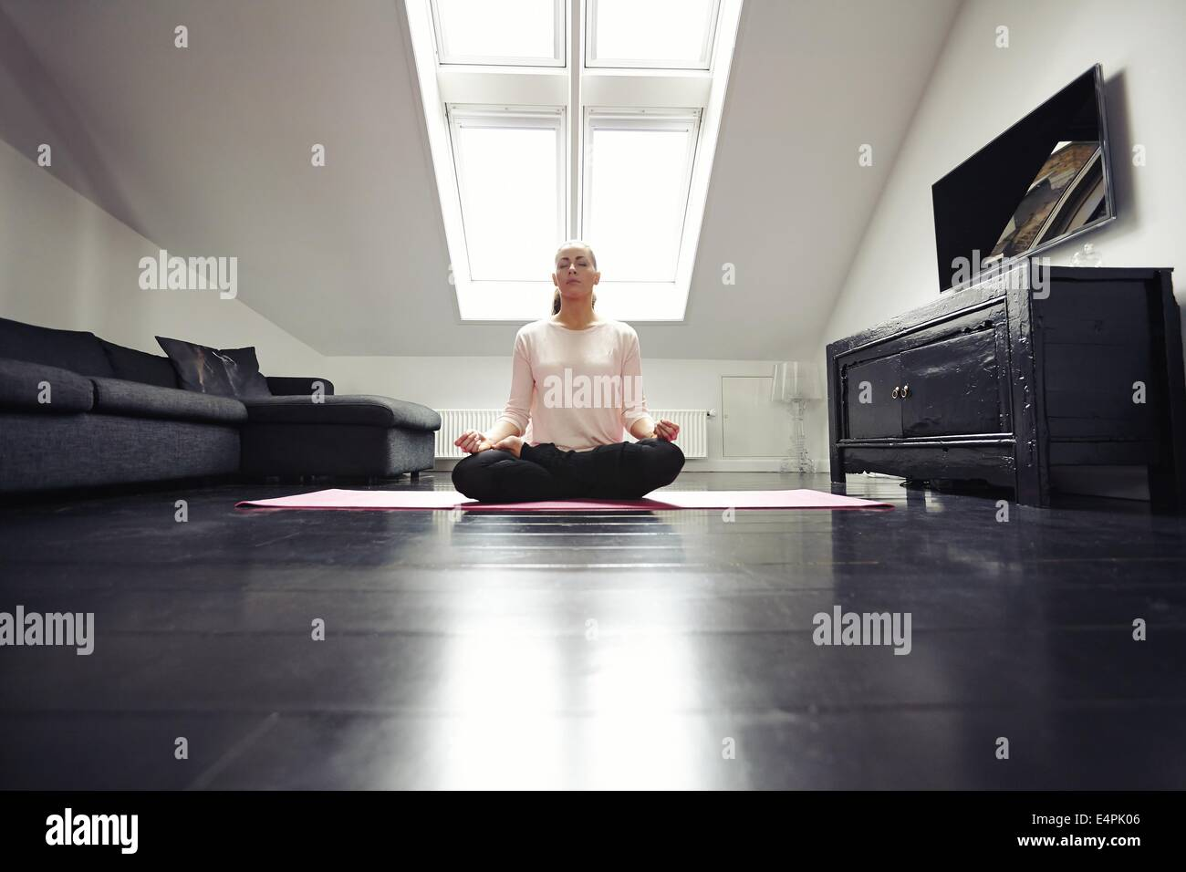 Portrait of healthy young woman exercising yoga in living room. Fitness female relaxing with yoga meditation at - Stock Image