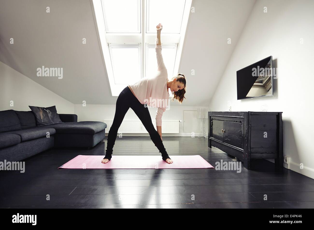 Fit young woman doing stretching exercise at her home. Healthy caucasian female model exercising in living room. - Stock Image