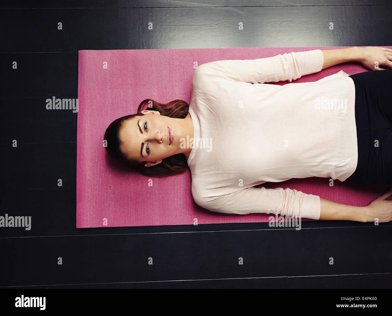 Top view of beautiful young woman lying on yoga mat after workout. Fit female relaxing on floor at home. - Stock Image
