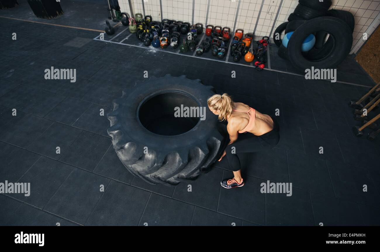 Top view of young female flipping heavy tire. Woman doing crossfit workout at gym. - Stock Image