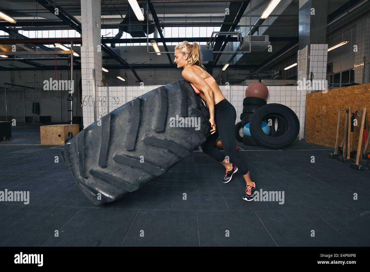 Fit female athlete flipping a huge tire. Muscular young woman doing crossfit exercise at gym. - Stock Image
