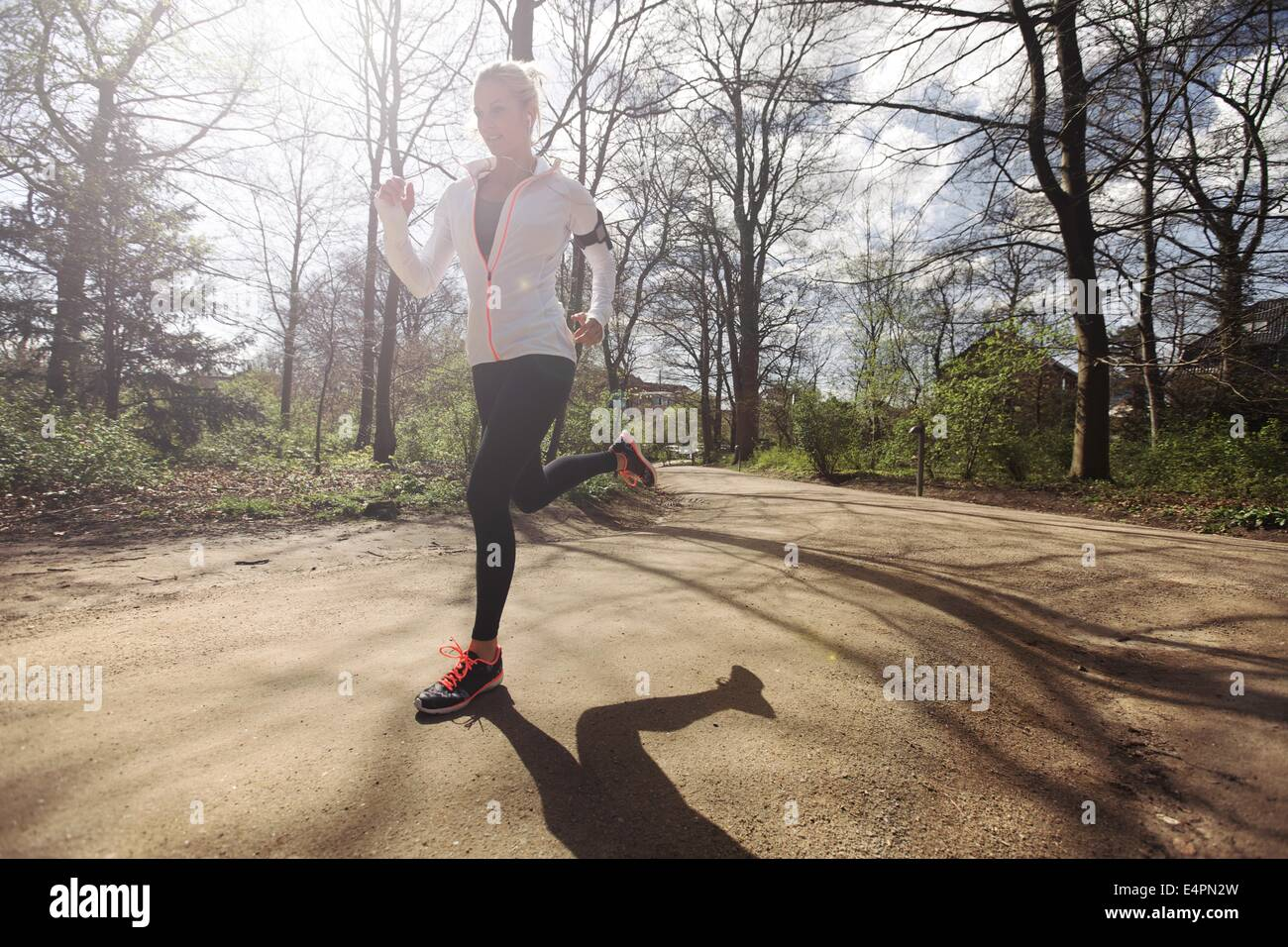 Young caucasian woman running outdoors in forest on a sunny day. Fit female athlete jogging in a park. Caucasian - Stock Image