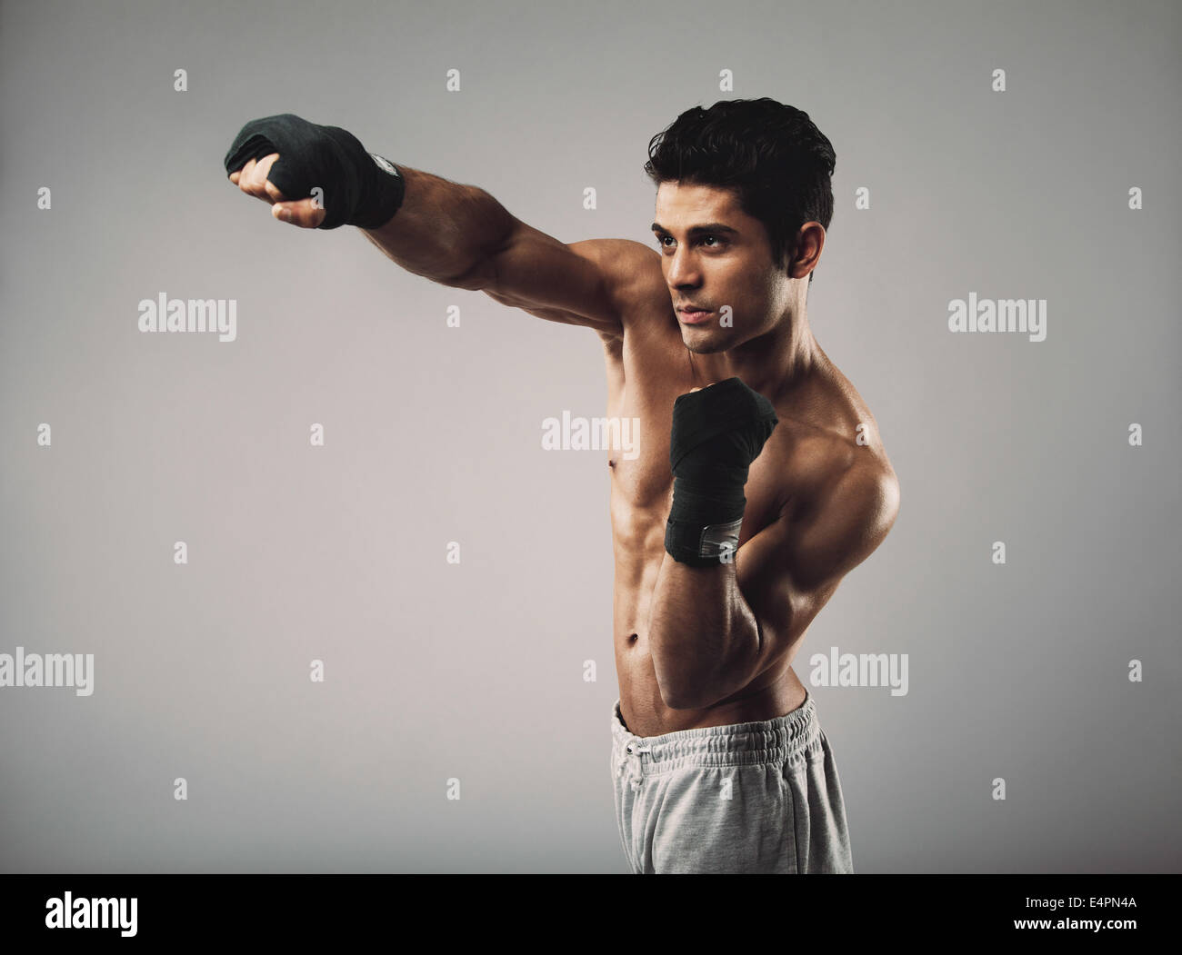 Fit young male model practicing shadowboxing.  Masculine young male athlete working out on grey background. - Stock Image