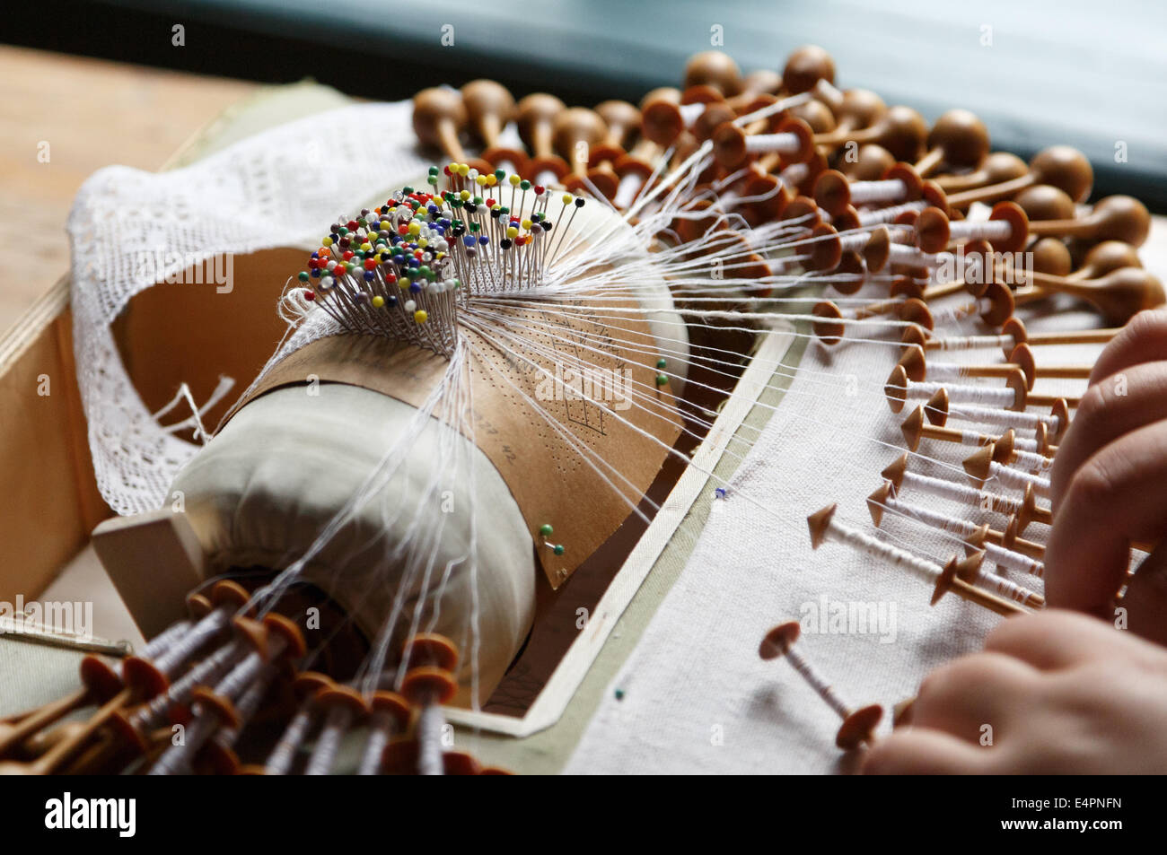 Bobbin lace being produced with the traditional method by hand with bobbins and a pillow with pins guiding the pattern. - Stock Image