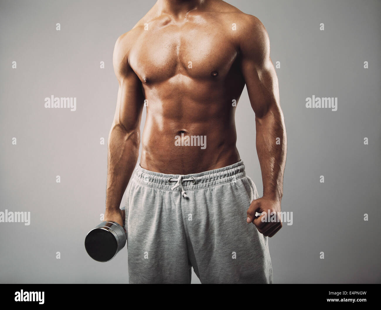 Studio shot of a male model in sweatpants holding dumbbell on grey background. Shirtless muscular man working out. - Stock Image