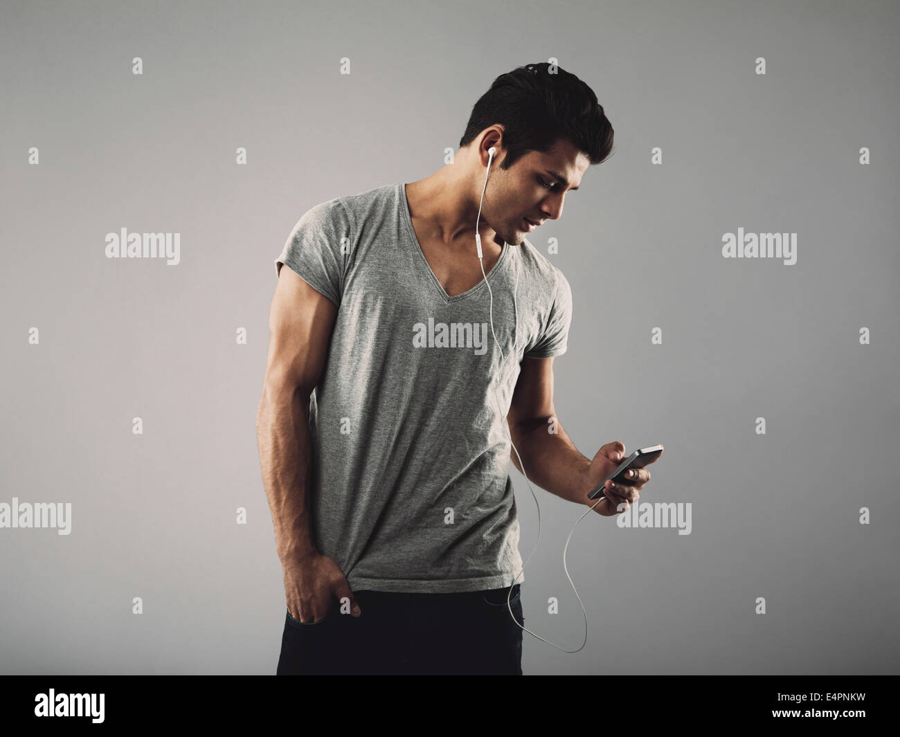 Handsome young man in casual t-shirt listening music on cell phone. Hispanic male model wearing earphones and listening - Stock Image