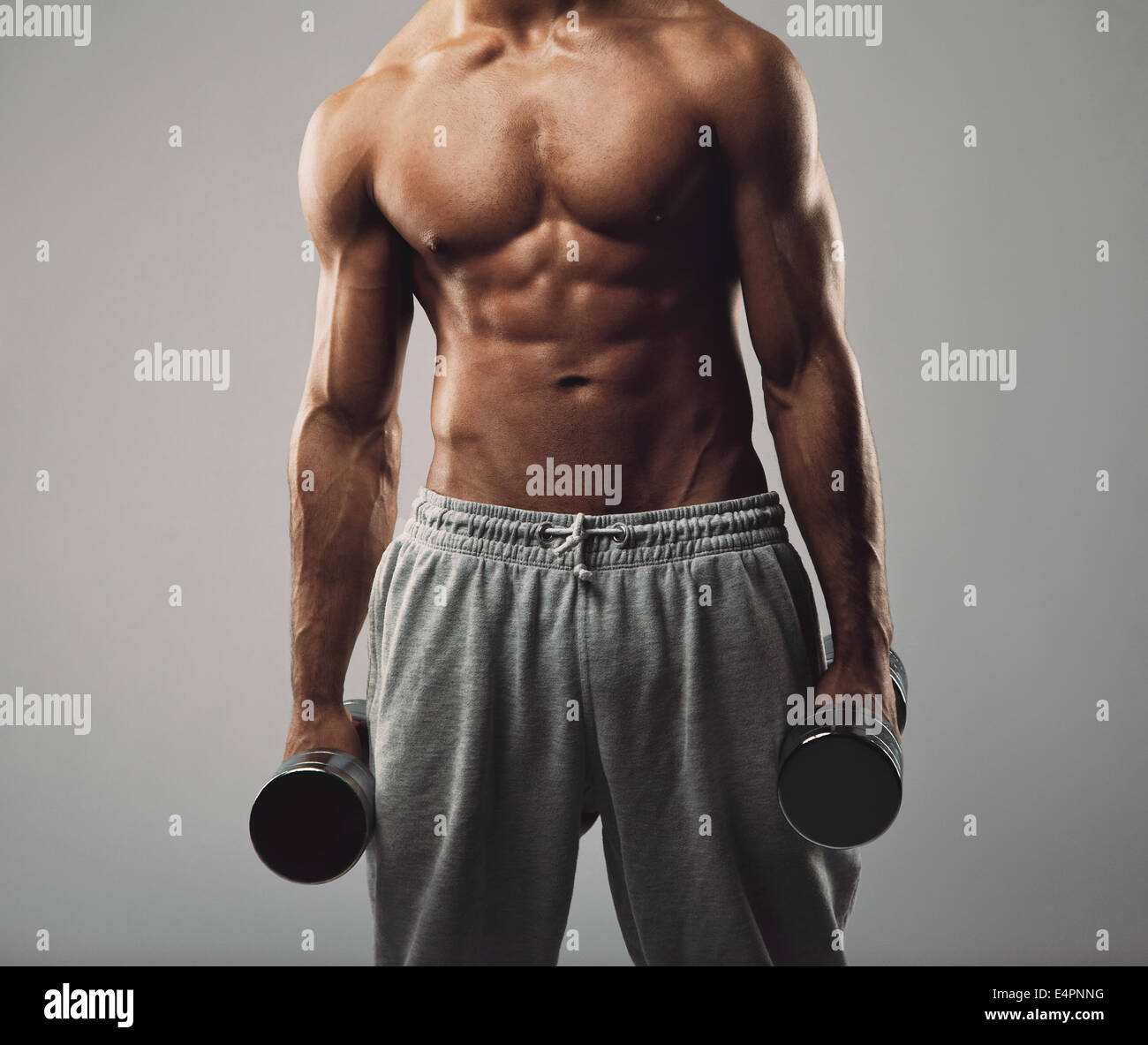 Cropped image of fitness male model holding dumbbells in both hands on grey background. Muscular young man working - Stock Image