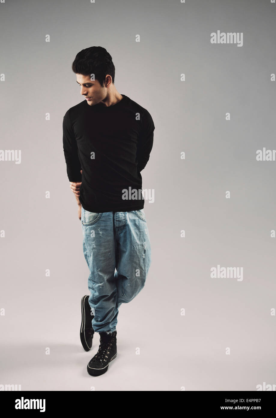 Full length portrait of hispanic young man in casuals posing. Male model looking down while standing on grey background. - Stock Image