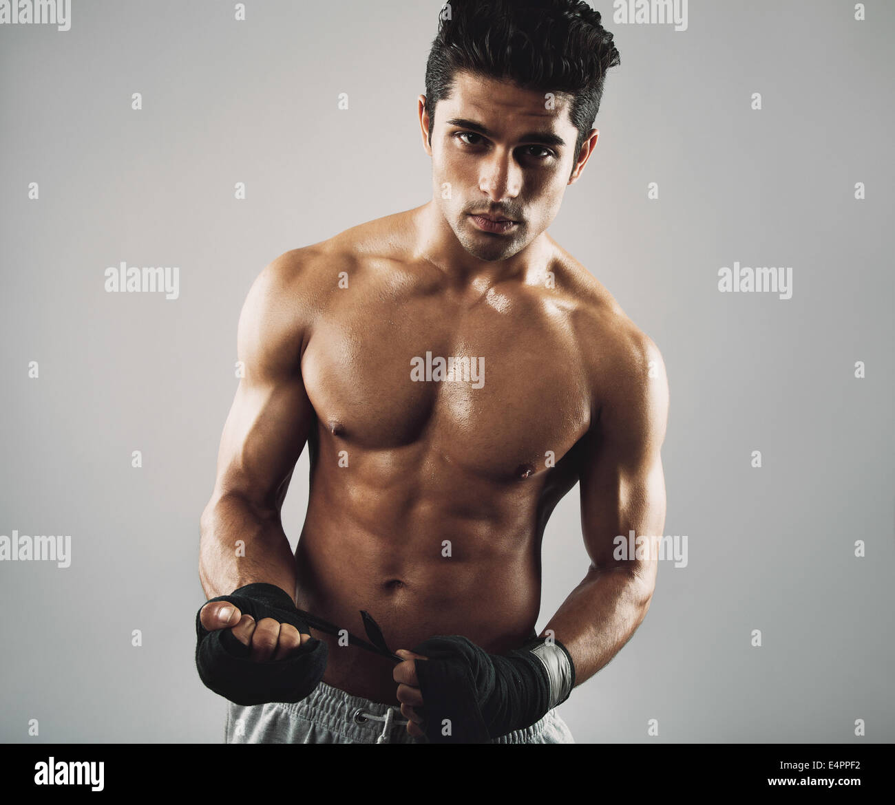 Portrait of tough young man wearing boxing gloves looking at camera. Hispanic male fitness model  shirtless on grey - Stock Image