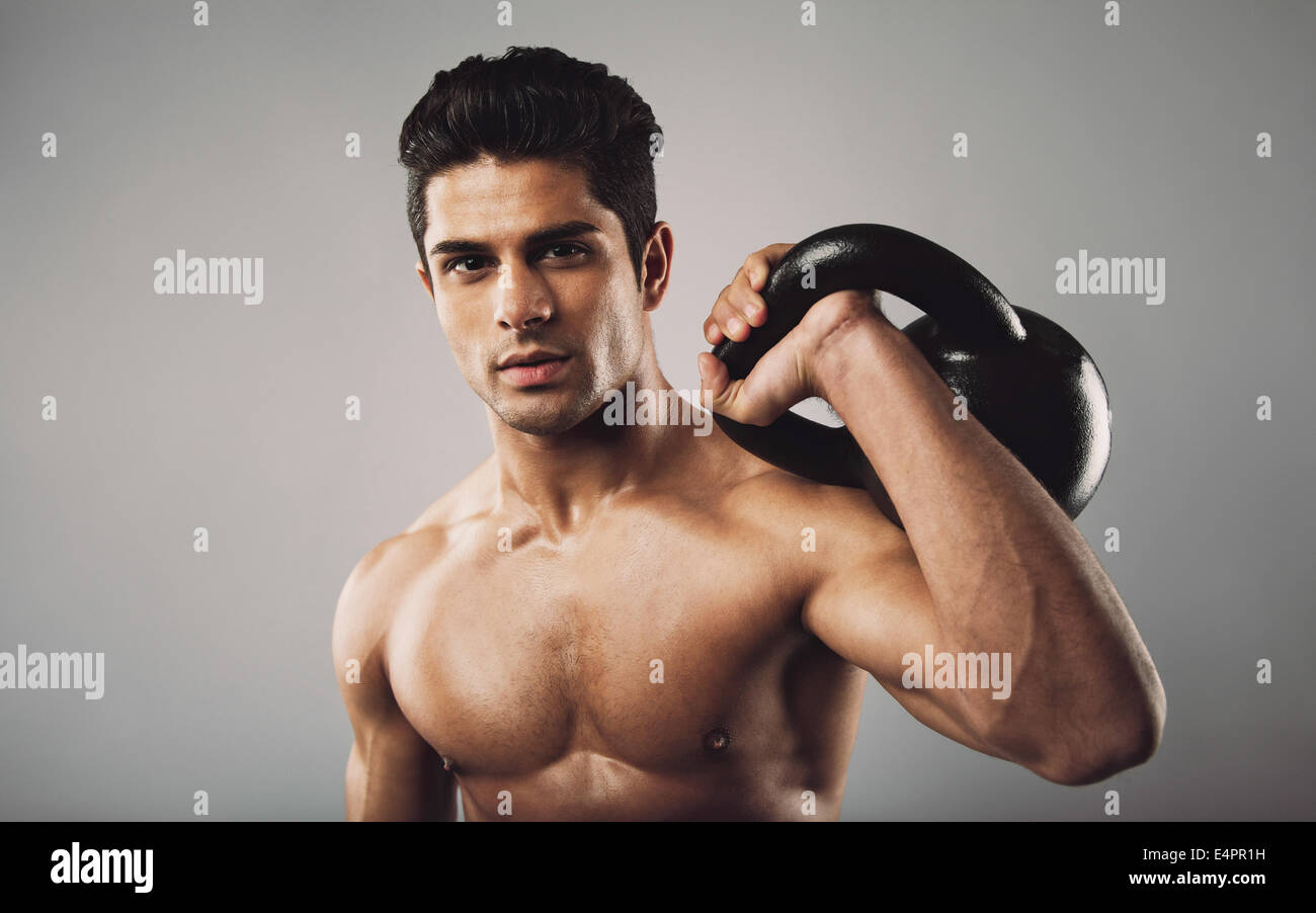 Portrait of hispanic fitness male model holding kettle bell on grey background. Shirtless young doing crossfit work - Stock Image