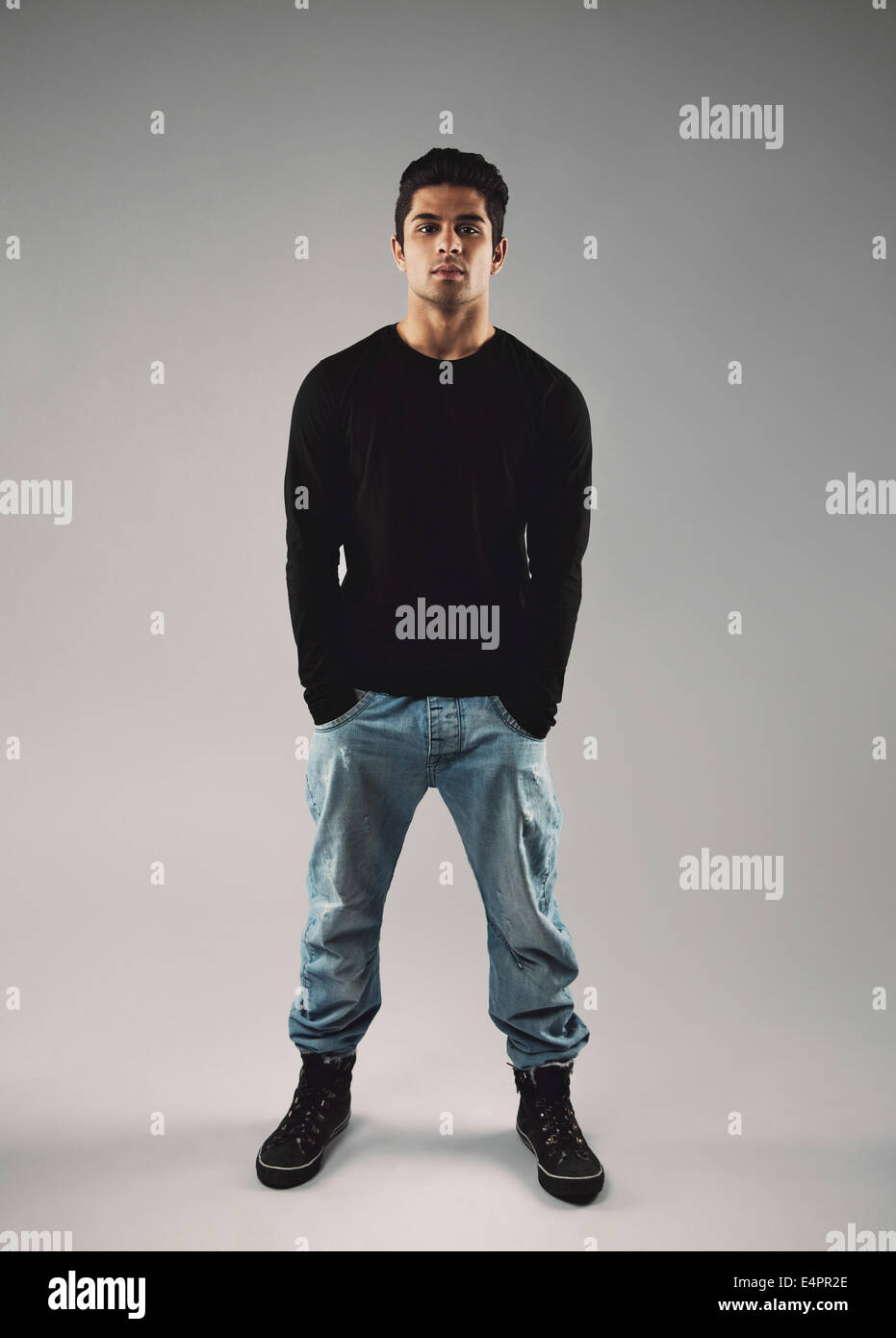 Full length portrait of stylish young man in casuals standing with his hands in pocket over grey background. - Stock Image