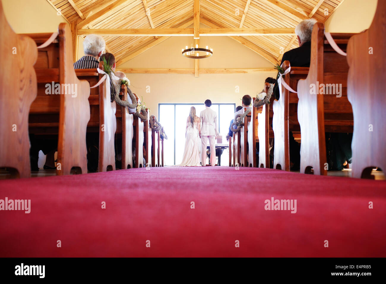 Red carpet lines the chapel aisle of the church in which a couple are wed - Stock Image