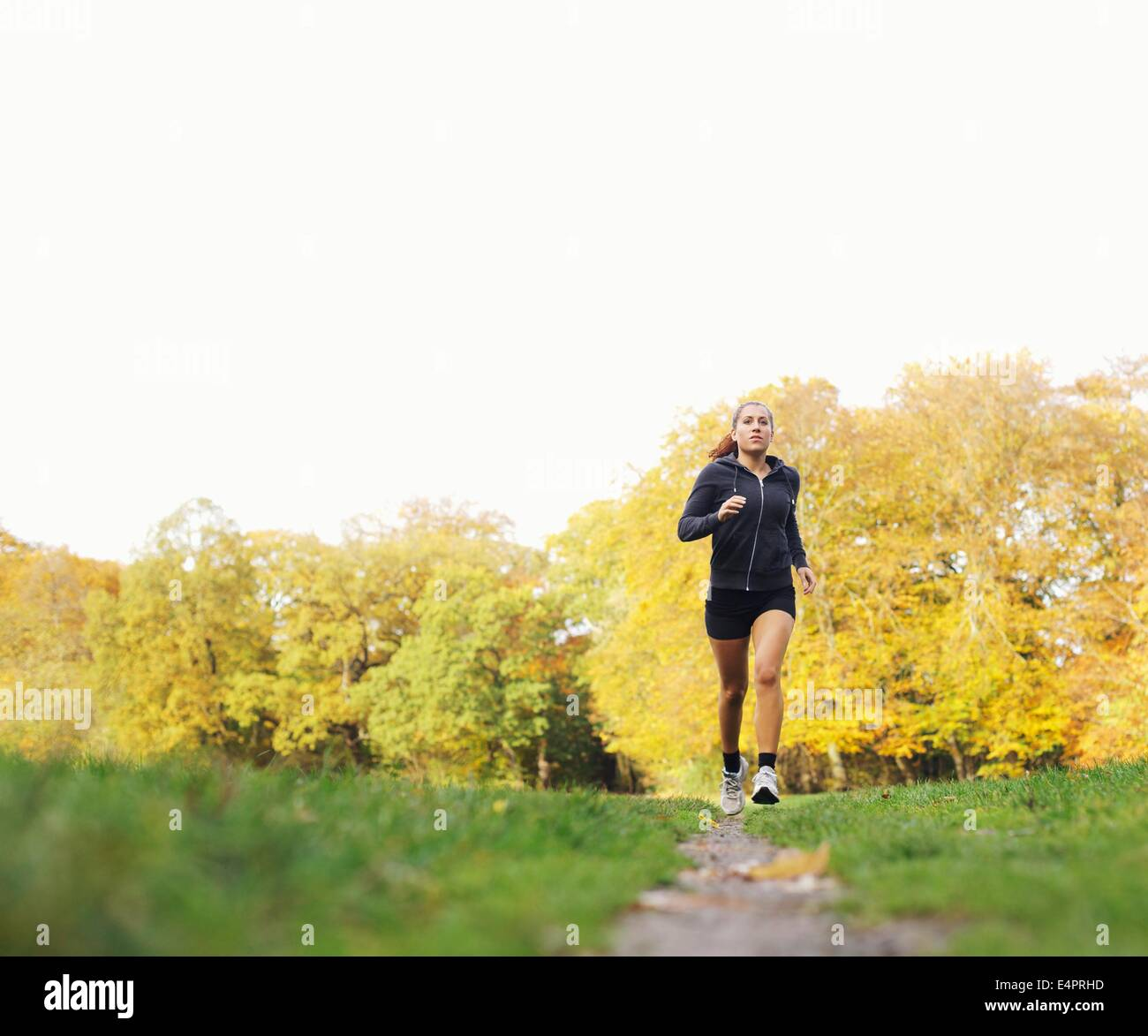 Young female runner running outside in park. Fitness model in sports clothing jogging outdoors. Health and fitness - Stock Image
