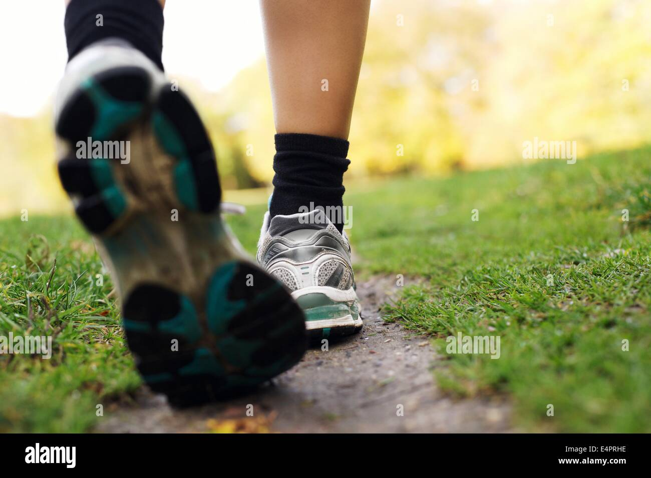 Feet of a runner in park. Woman walking in the park, close up of feet. Fitness and exercising training. - Stock Image
