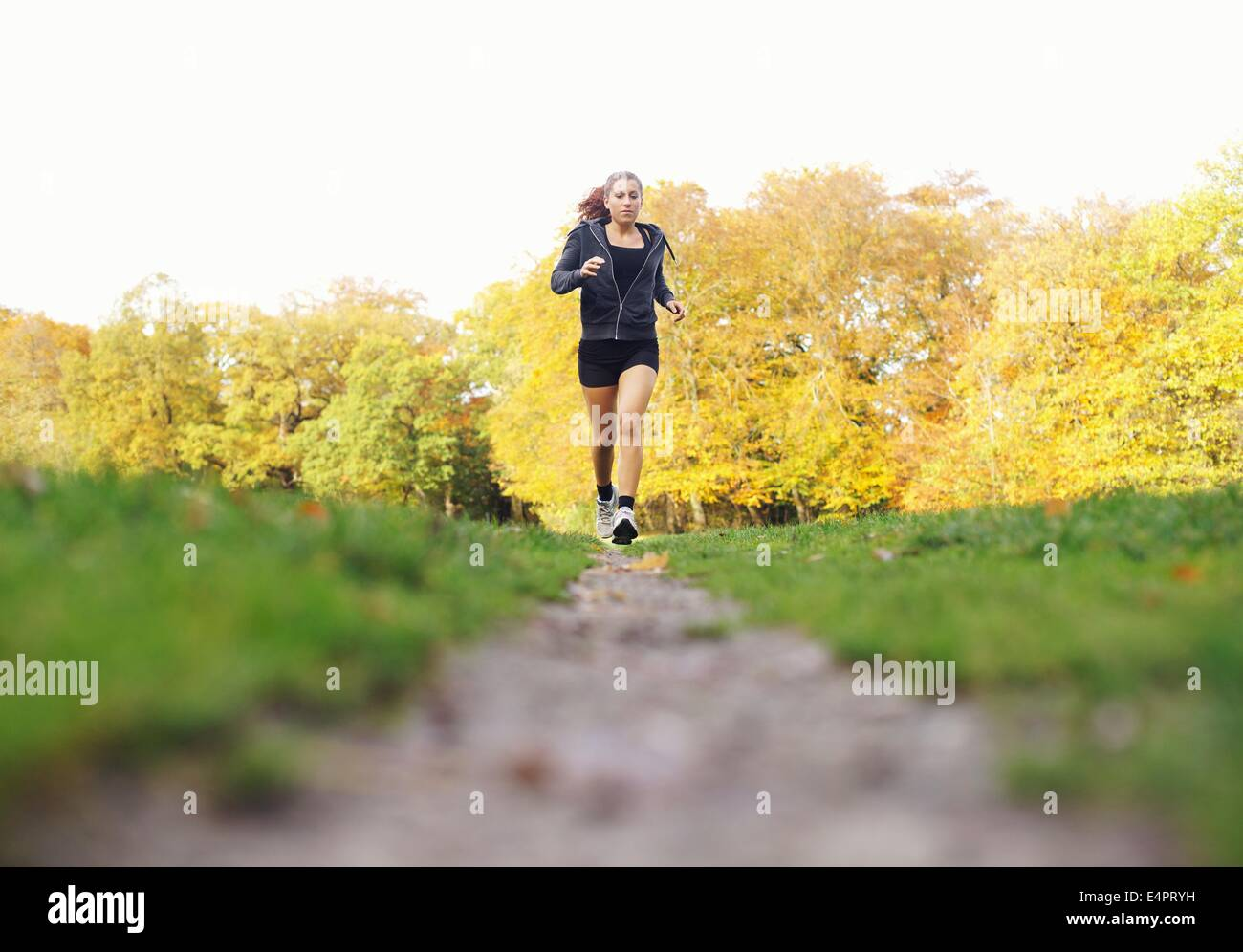 Fit young woman jogging in a park on a summer day. Healthy female athlete exercise running in park - Outdoors - Stock Image
