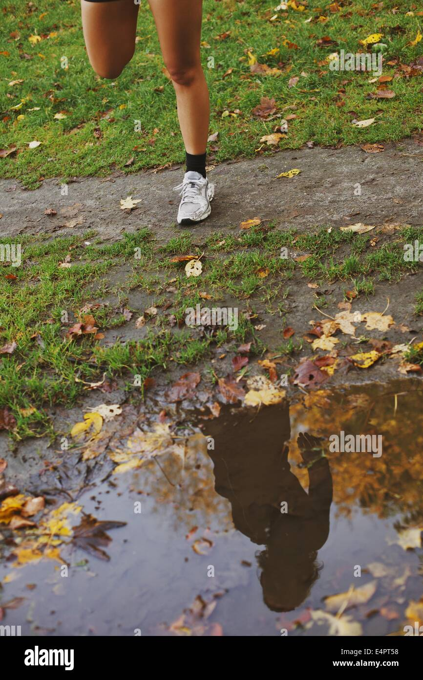 Reflection of young woman in a puddle of water in park. Low section of fitness female legs doing stretching exercise - Stock Image