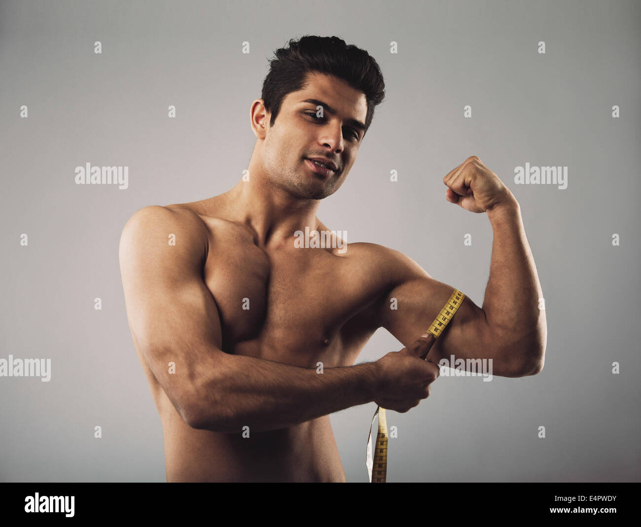 Fit hispanic male model measuring his body. Masculine young male measuring biceps with tape measure on grey background. - Stock Image