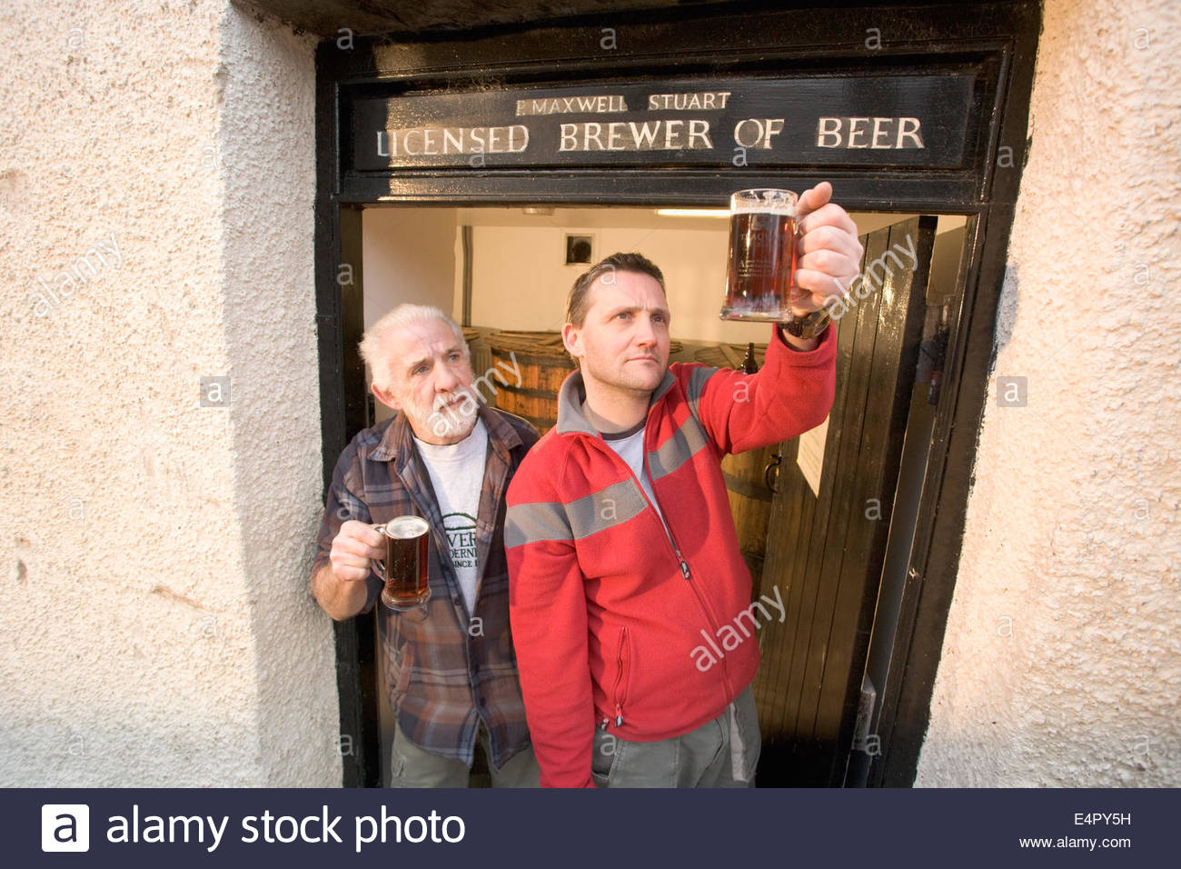 Two brewers raise a glass in the doorway to the tun room at the original brewhouse at Traquair House Brewery, Traquair - Stock Image