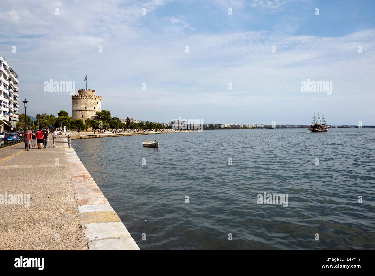 People walks past the city`s landmark, the White Tower in Thessaloniki, Greece. - Stock Image