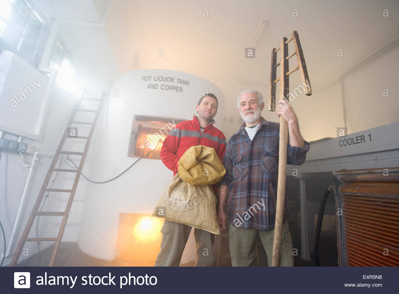 Two brewers pose for a photograph by the Hot Liquor Tank at the original brewhouse at Traquair House Brewery, Traquair - Stock Image