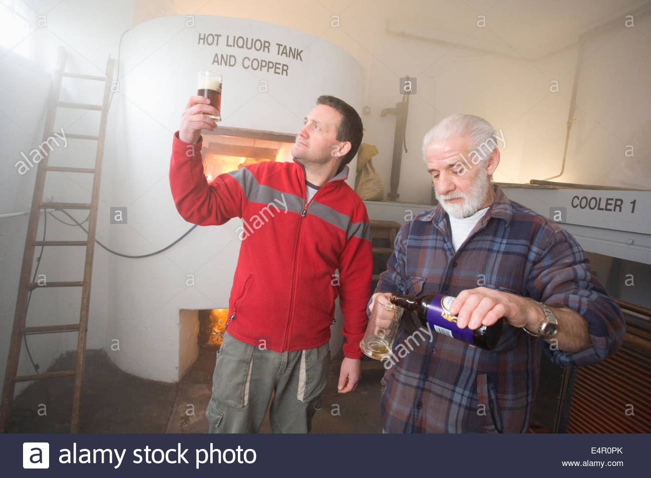 Two brewers check the quality of the finished product by the Hot Liquor Tank at the original brewhouse at Traquair - Stock Image