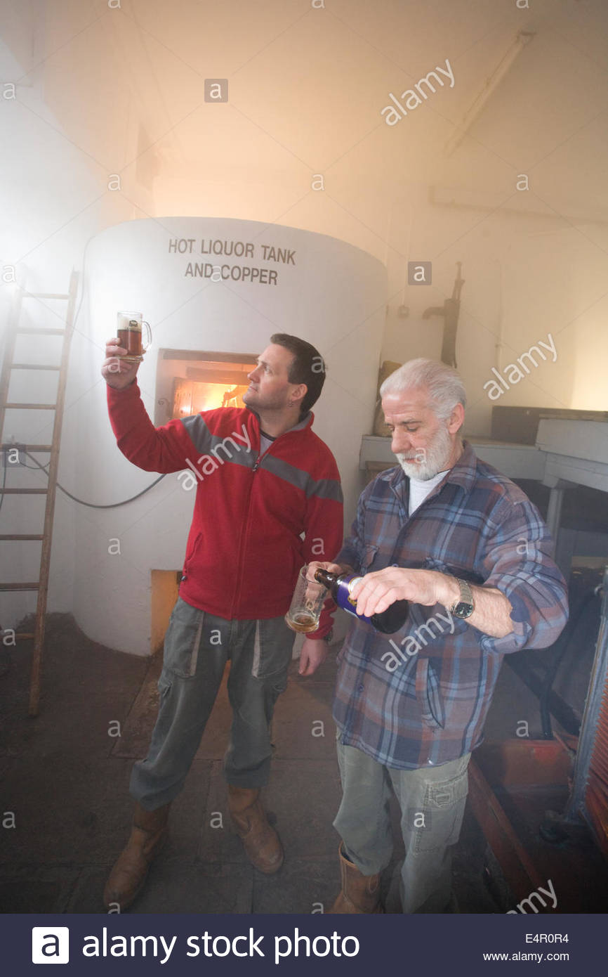 Two brewers check the quality of the finished product by the Hot Liquor Tank at the original brewhouse at Traquair Stock Photo