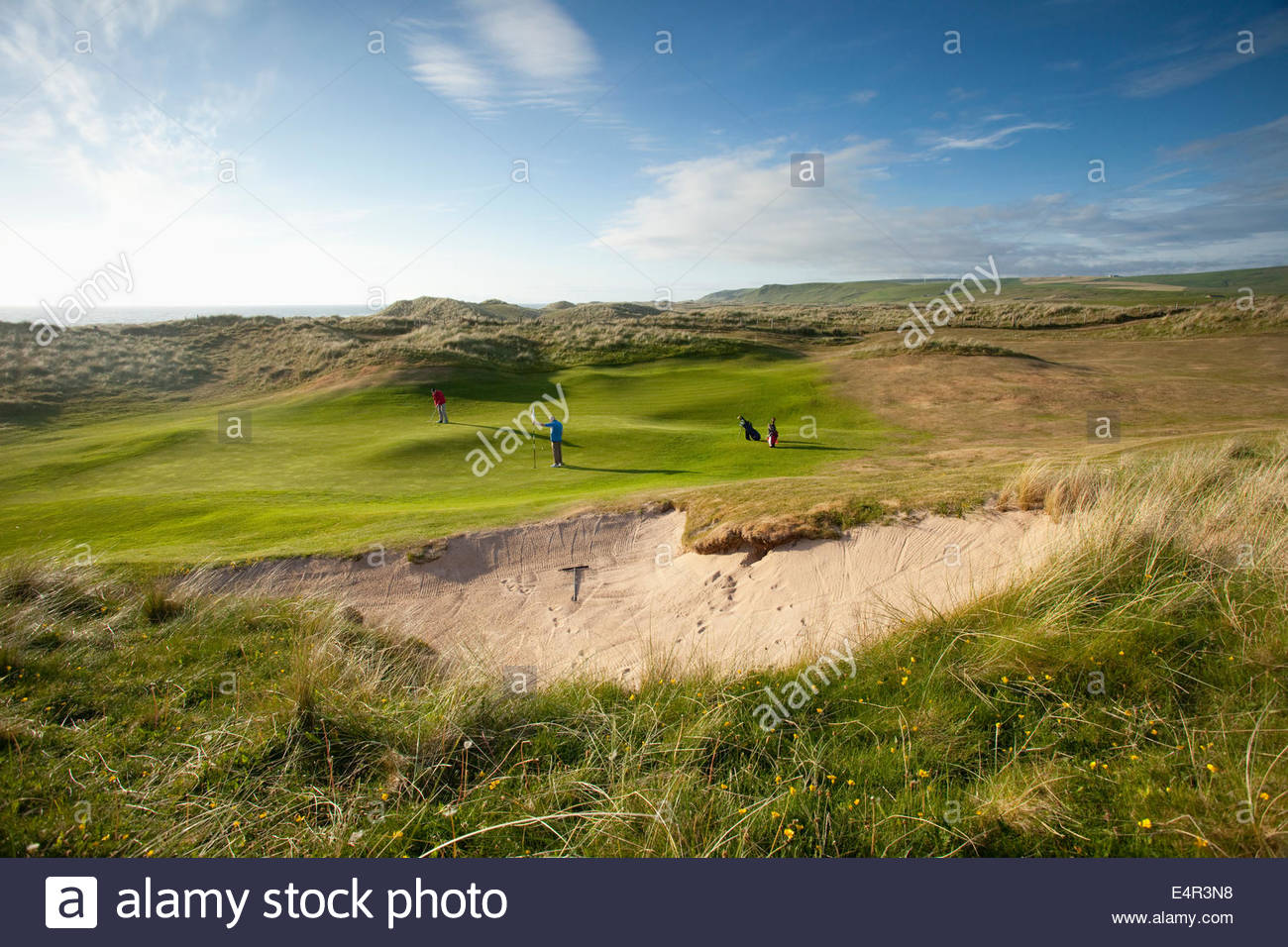 Two golfers play one of the holes on the Machrihanish Dunes Golf Club, Machrihanish, Kintyre, Argyll, Scotland. - Stock Image