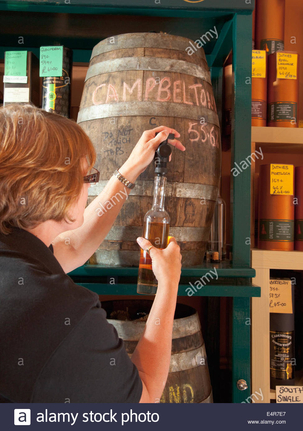 The shop assistant fills a bottle with whisky at the shop at the Springbank Distillery, Campbeltown, Kintyre, Argyll, - Stock Image