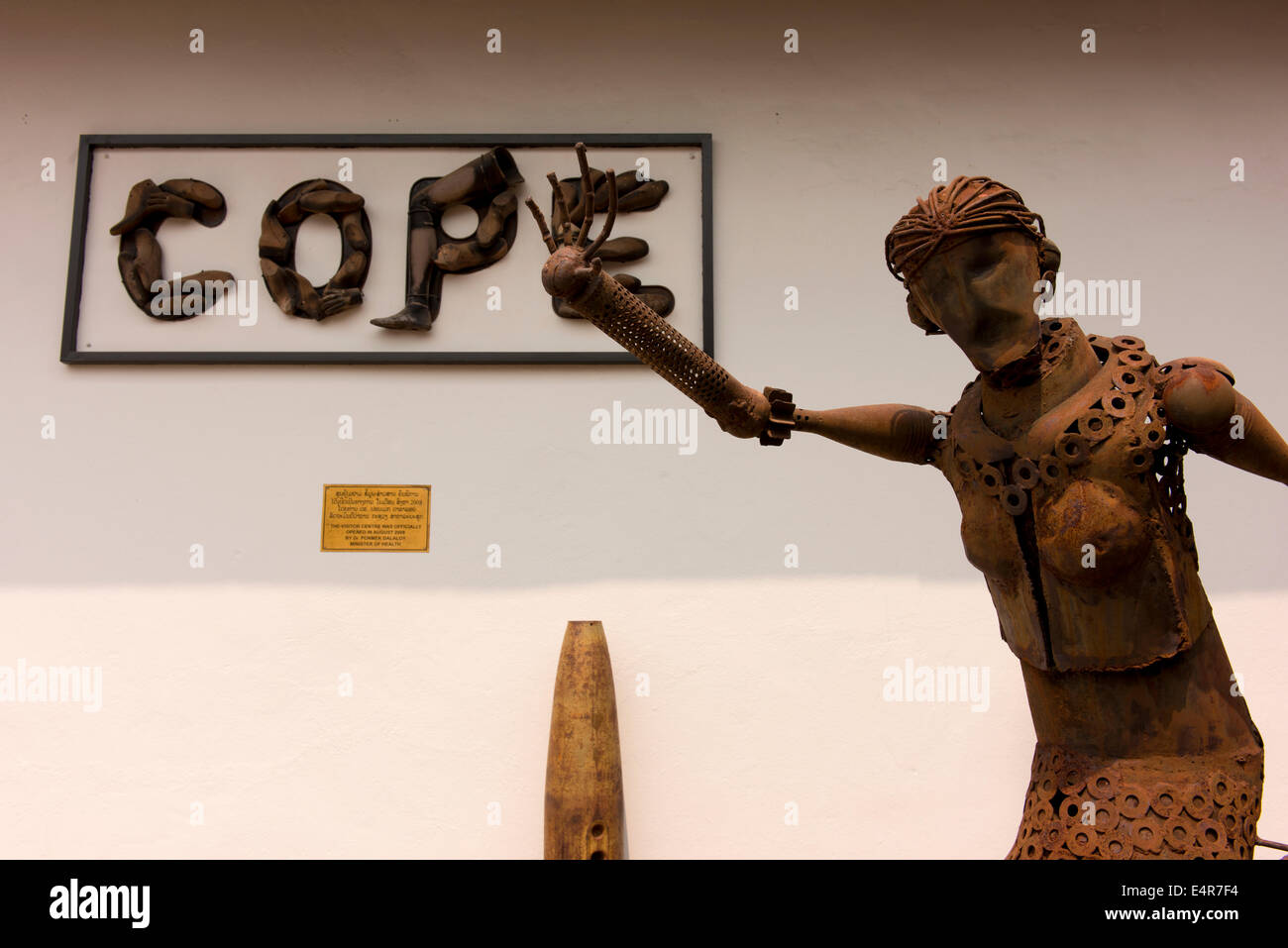 Statue made of unexploded ordnance (UXO) of a woman outside the COPE center which helps survivors of UXO. - Stock Image