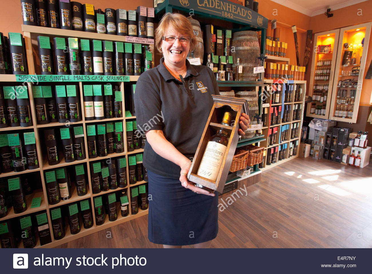 The shop assistant poses for a photograph with a bottle of 1919 single malt whisky valued at £50,000 at the - Stock Image