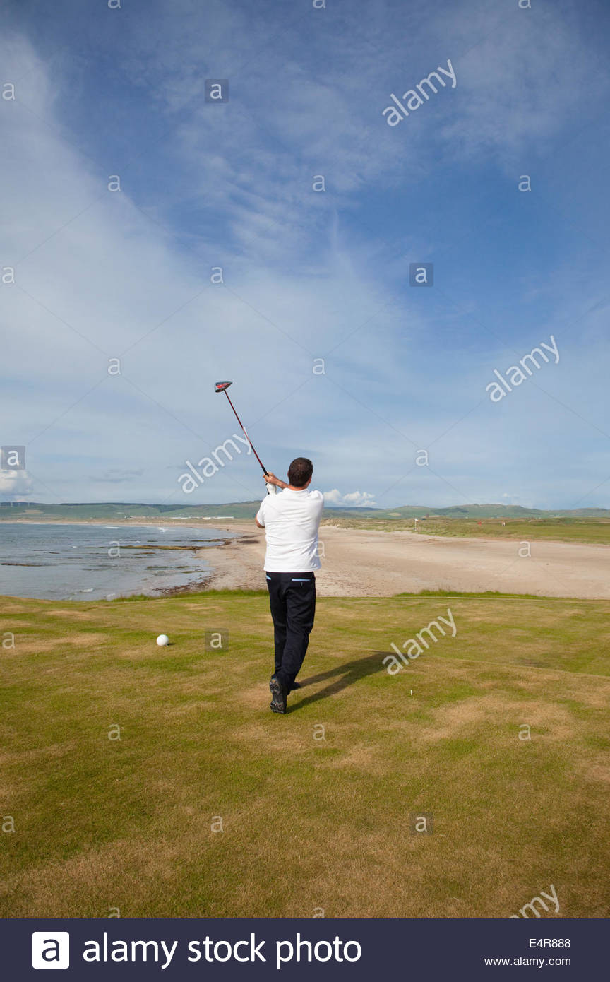 Teeing off for the first hole, The Battery - reputably the best opening hole in the world on the Machrihanish Dunes - Stock Image