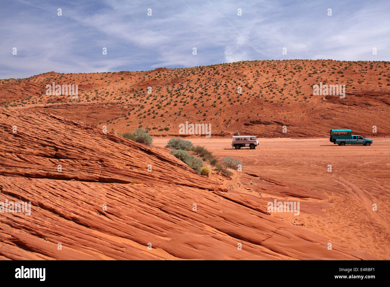 Tour groups being driven up dry sandy creek bed towards Upper Antelope Canyon, near Page, Navajo Nation, Arizona, - Stock Image