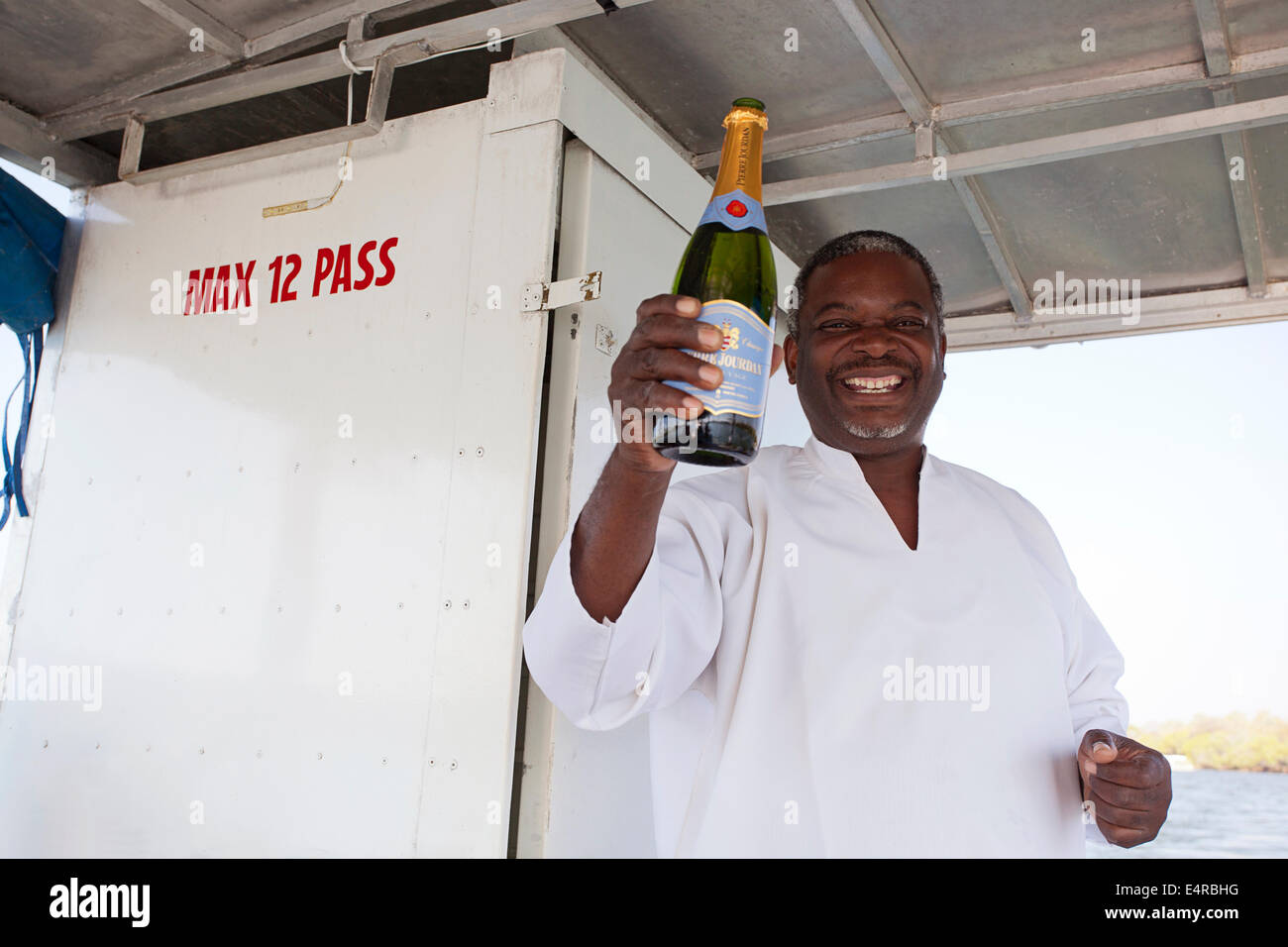 Captain of the boat holding up a bottle of Champaign and smiling - Stock Image