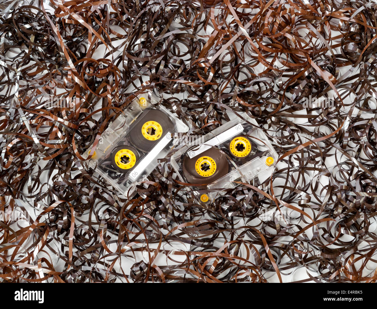 Two compact tape cassettes with blank labels and no branding in the midst of a mass of tangled and broken tape - Stock Image