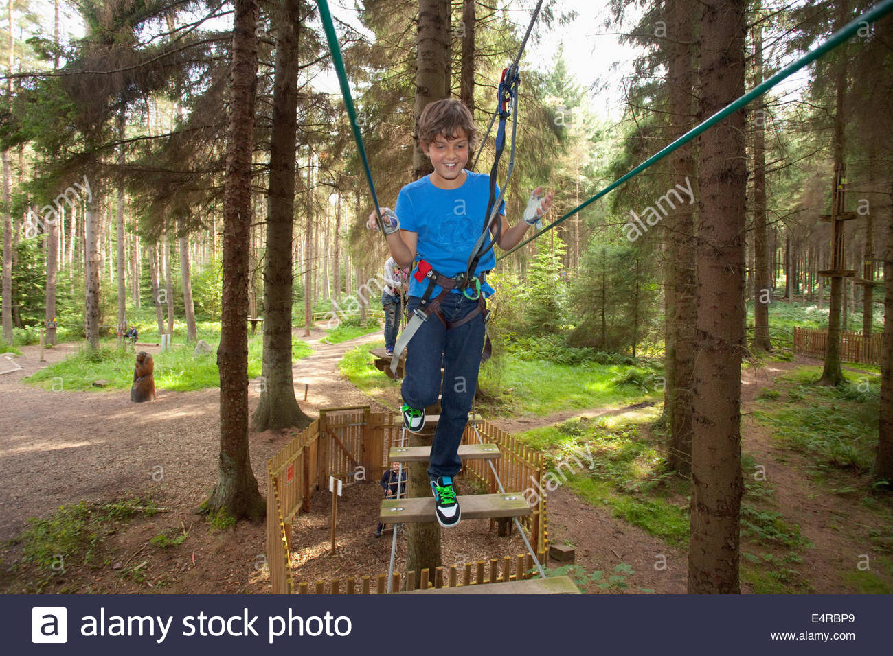 A youngster enjoys a tree top adventure course, West Lothian, Scotland. Stock Photo