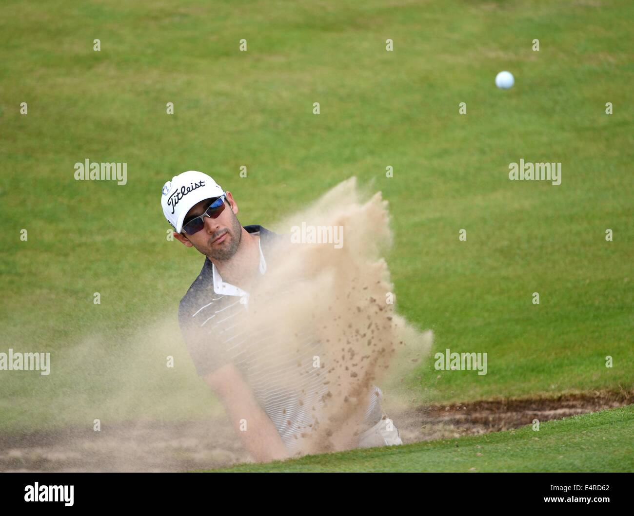 Hoylake, UK. 16th July, 2014. The Open Golf Championship. Cameron Tringle [USA] splashes out of the bunker on the Stock Photo