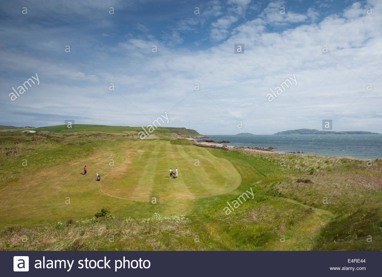 Three women golfers playing one of the holes at the Dunaverty Golf Club by Southend, Kintyre, Argyll, Scotland. - Stock Image