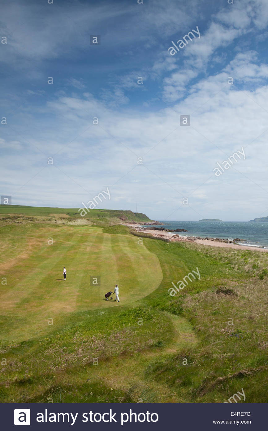 Two women golfers playing one of the holes at the Dunaverty Golf Club by Southend, Kintyre, Argyll, Scotland. - Stock Image