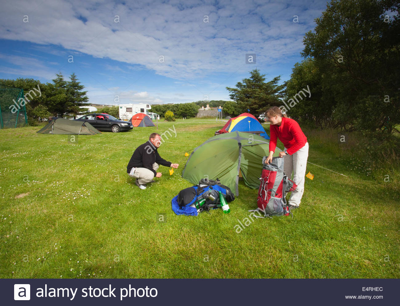 A couple pack up their tent at the Pickaquoy Caravan and Camping Site, Kirkwall, Mainland, Orkney, Scotland. - Stock Image