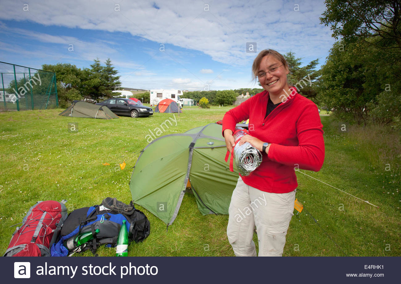 A woman packs up her tent at the Pickaquoy Caravan and Camping Site, Kirkwall, Mainland, Orkney, Scotland. - Stock Image