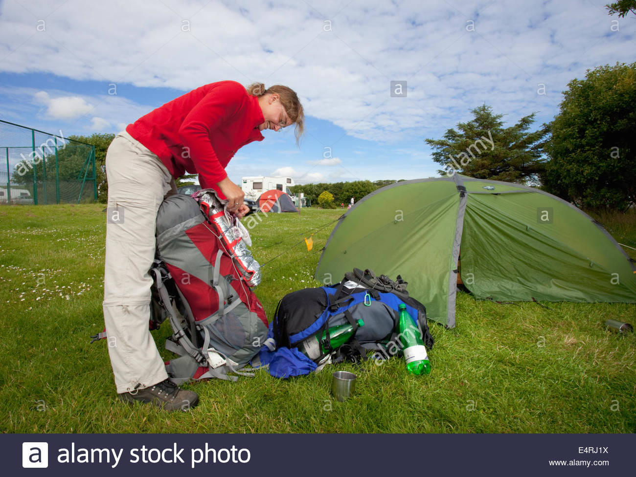 A couple by their tent at the Pickaquoy Caravan and Camping Site, Kirkwall, Mainland, Orkney, Scotland. - Stock Image