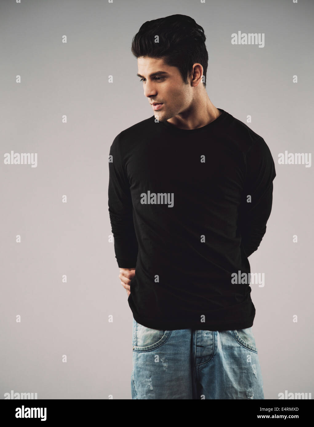 Portrait of young man in casuals looking away at copyspace. Hispanic male model on grey background - Stock Image