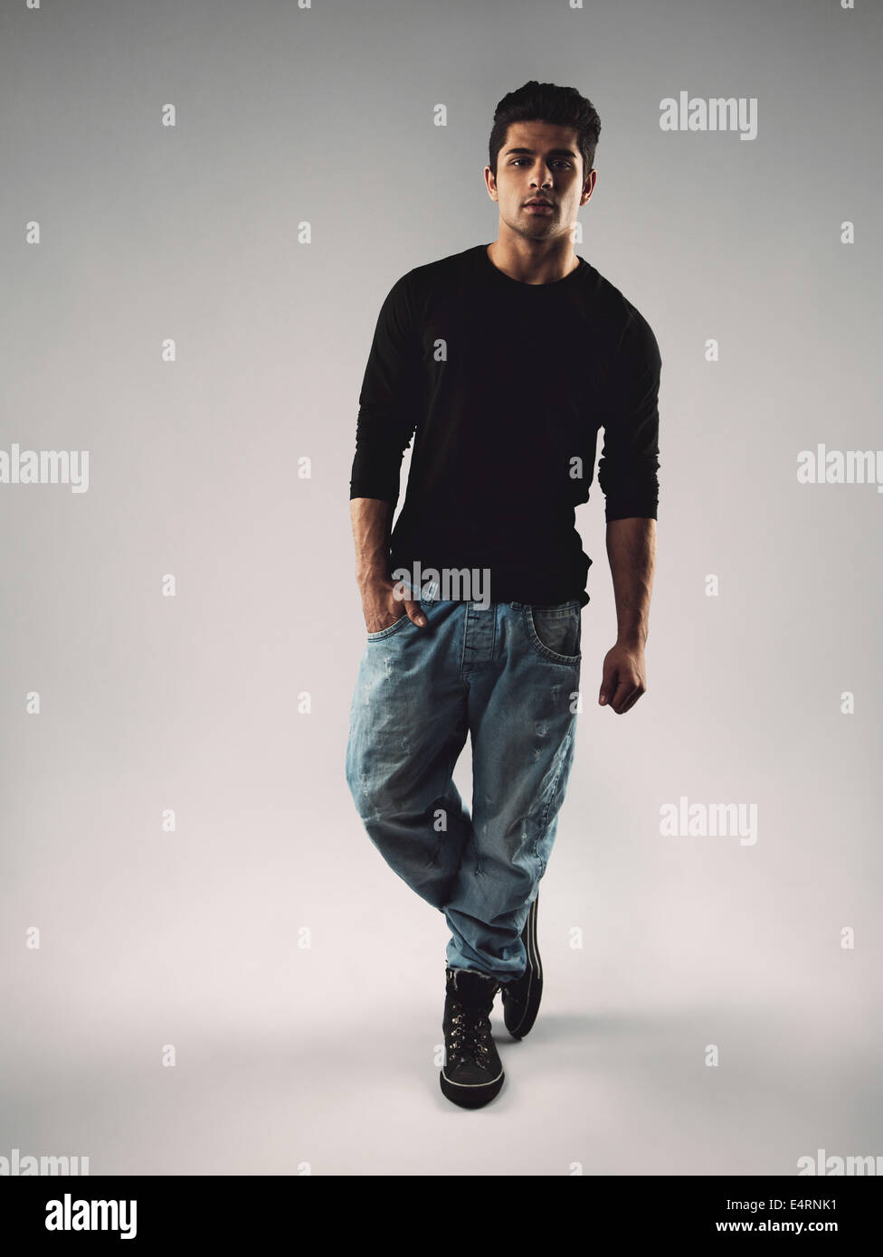 Full length portrait of stylish young man in casuals looking at camera. Hispanic male model posing on grey background. - Stock Image