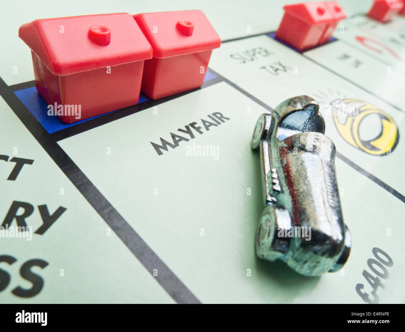 'MAYFAIR' on a Monopoly board with the car and two hotels. - Stock Image