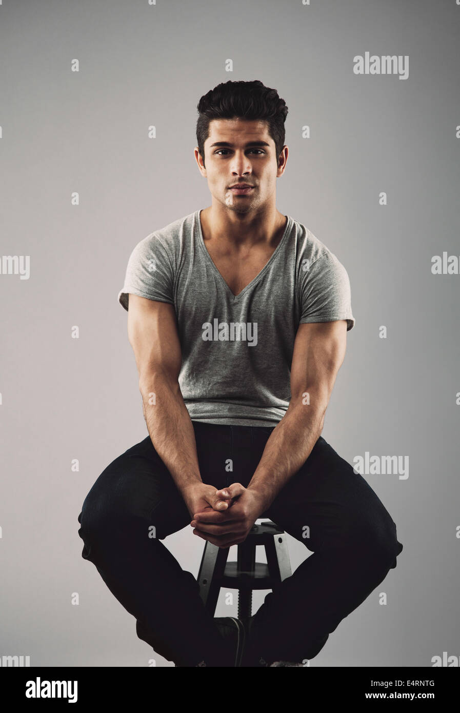Portrait of muscular young male model sitting on stool. Hispanic young man over grey background. - Stock Image