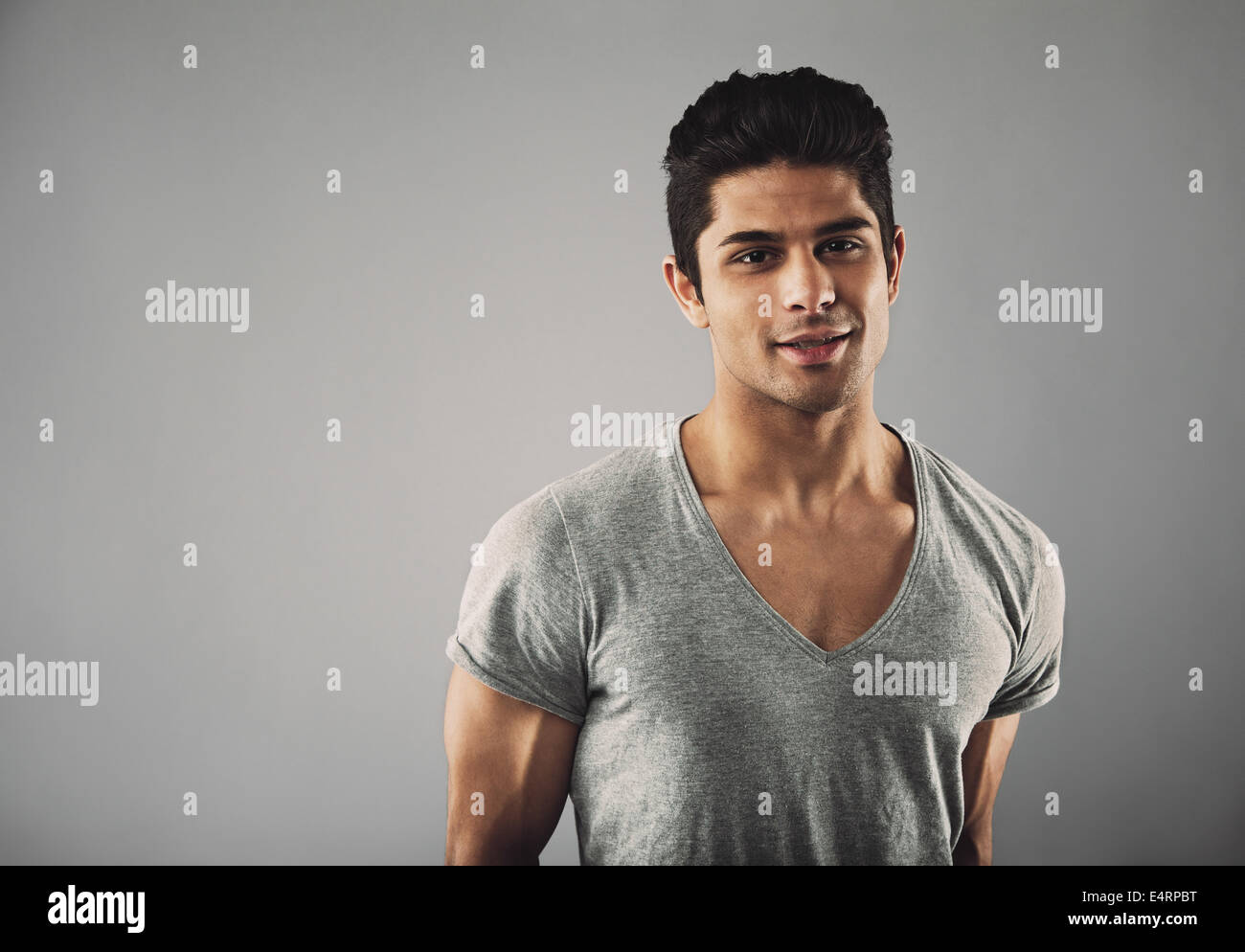 Portrait of handsome young hispanic male fashion model posing against grey background with copy space. - Stock Image