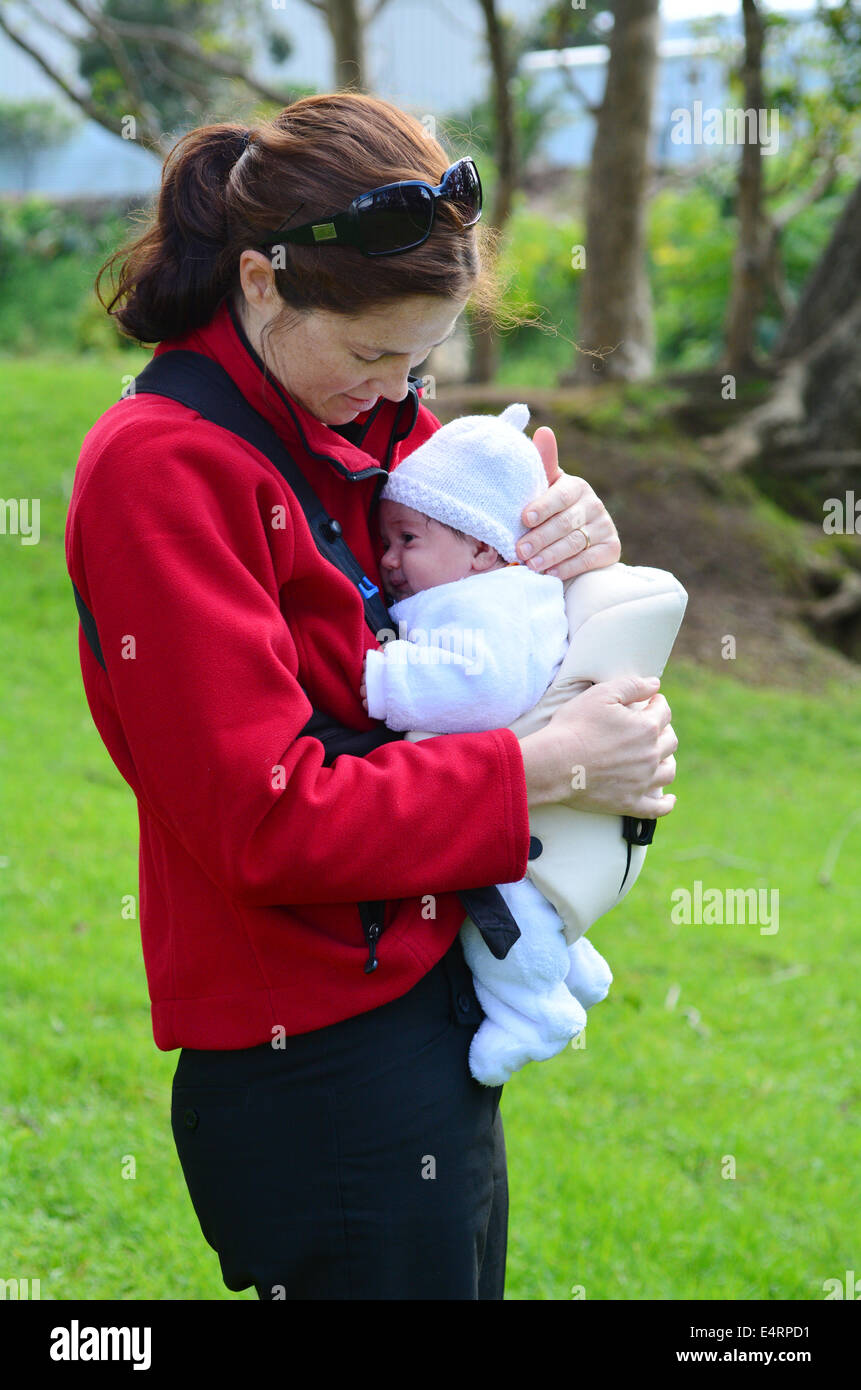 Mother carry newborn baby on baby carrier. concept photo of motherhood, baby, newborn. - Stock Image