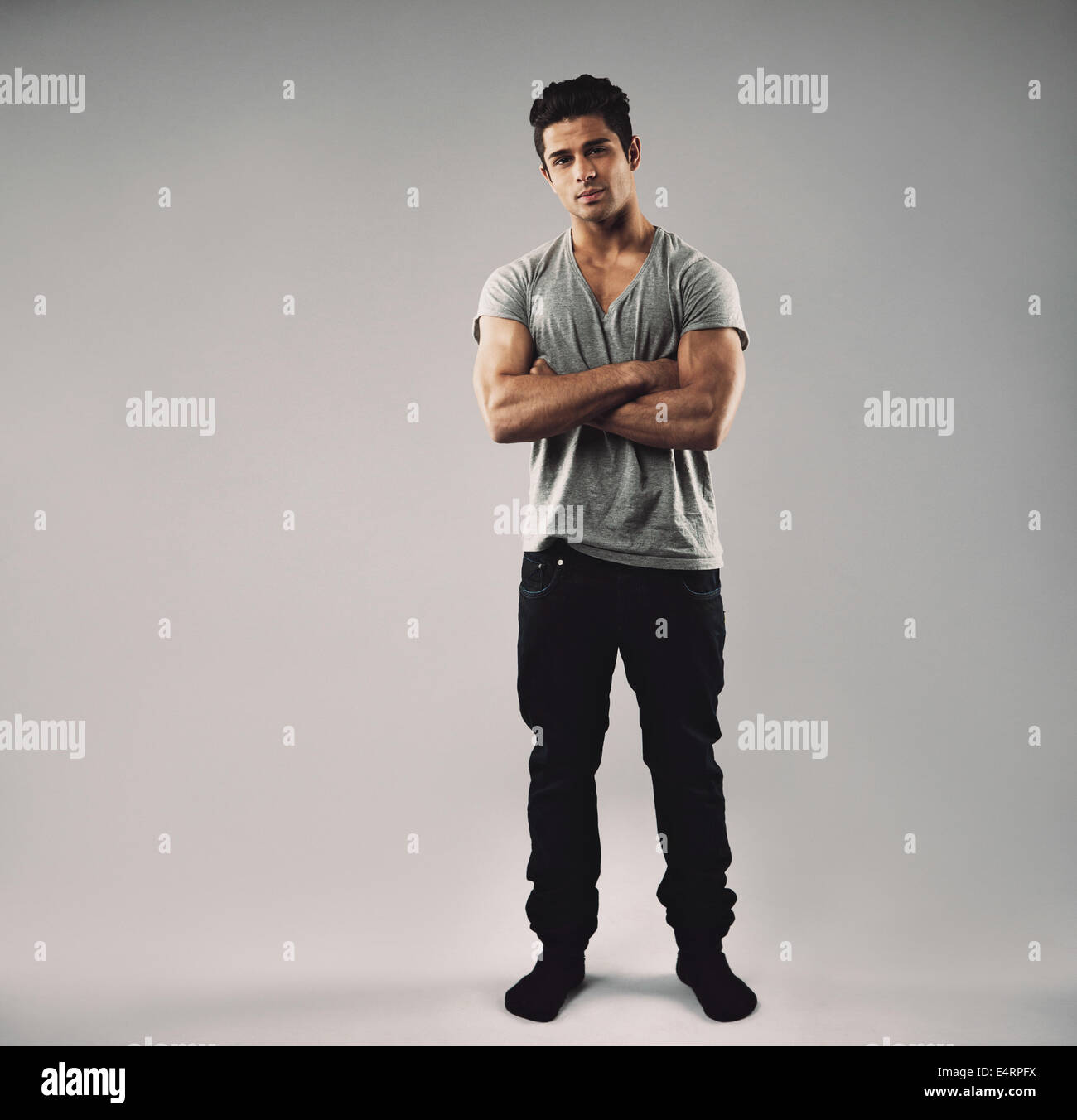 Full length portrait of muscular young man standing with his arms crossed. Hispanic mate model in casuals with copy - Stock Image