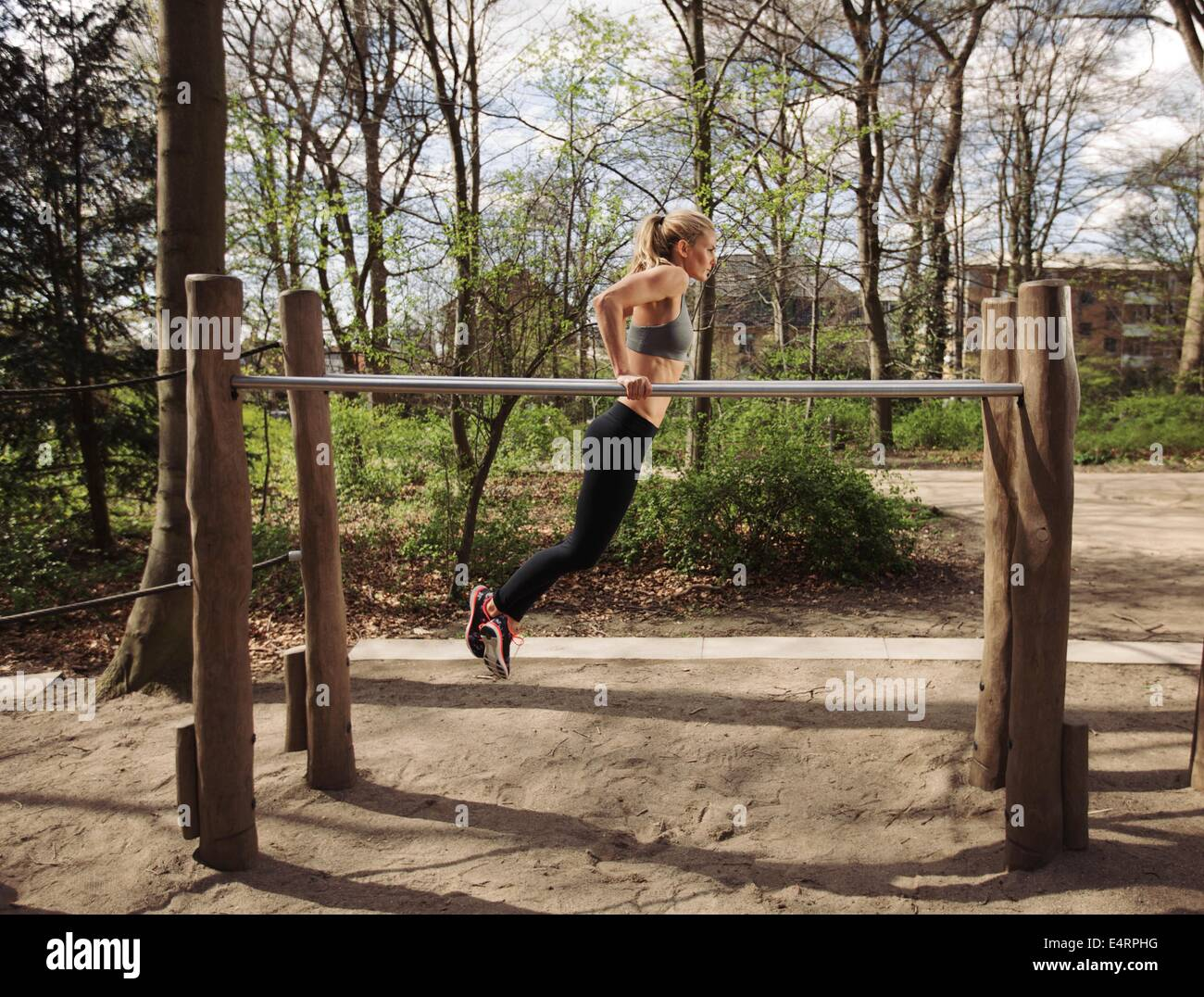 Side view of muscular young woman doing triceps dips on parallel bars at park. Caucasian female fitness model exercising - Stock Image